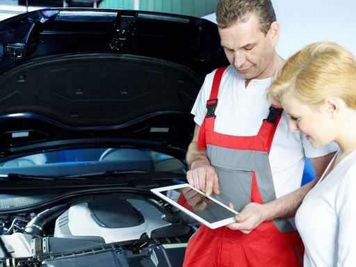 Motor mechanic shows customer repair details on touchpad